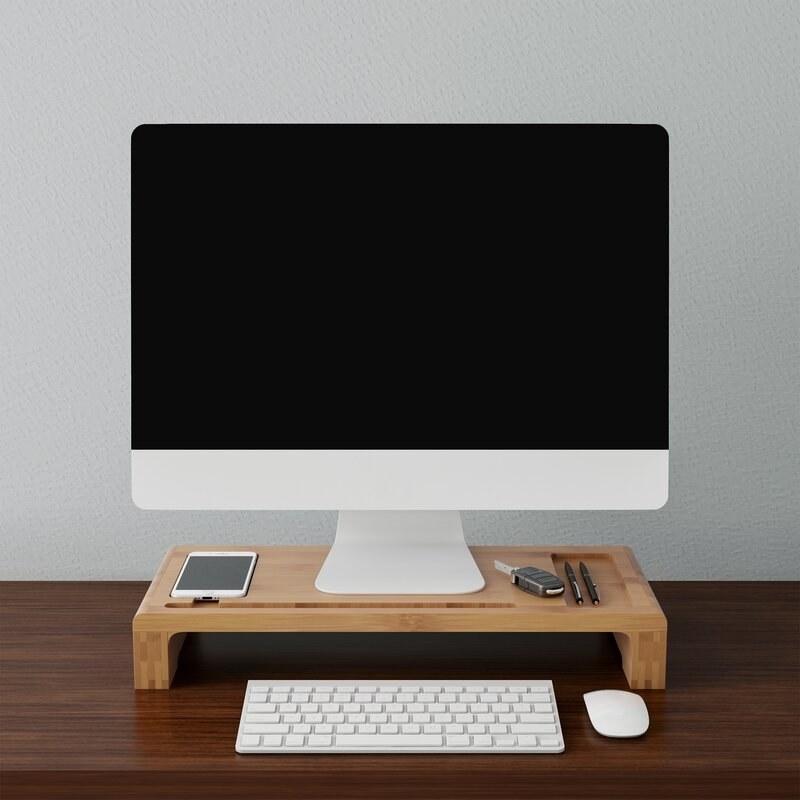 A bamboo monitor riser holding pens, a car key, a phone, and a computer monitor