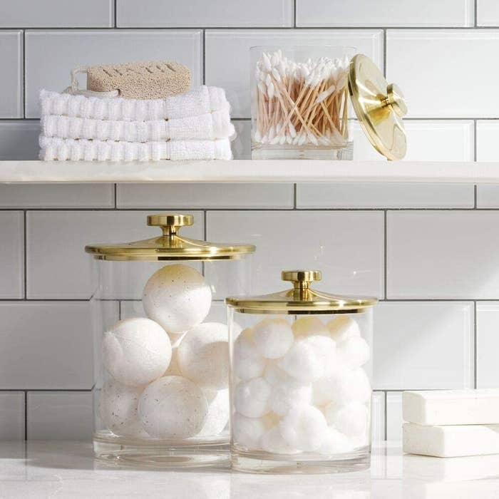 A large and medium clear jar with a gold lid sitting on a counter with bath bombs and cotton balls in them and then a small jar on the shelf above with q-tips in it