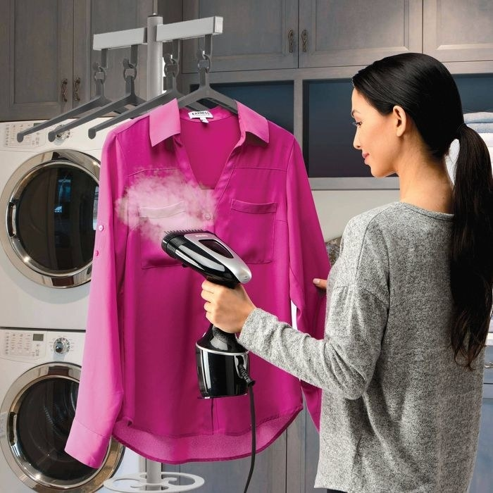 person using a garment steamer to steam a pink blouse