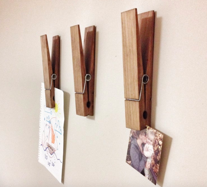 A trio of large paper clips hung on a wall and holding family photos and kids' drawings