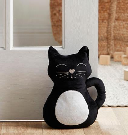 A smiling cat door stopper props open a large door