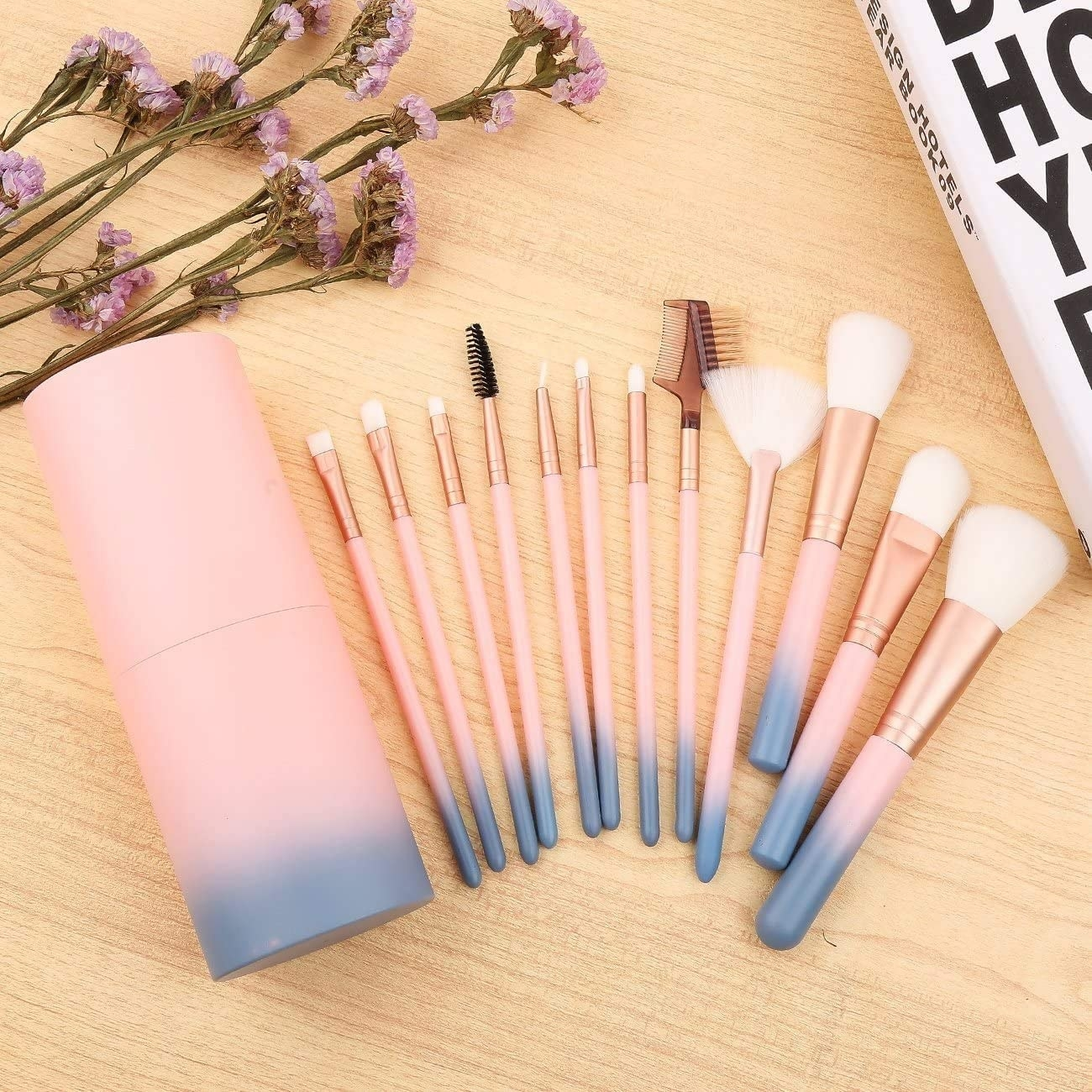 A flatlay of all the makeup brushes fanned out on a wooden counter