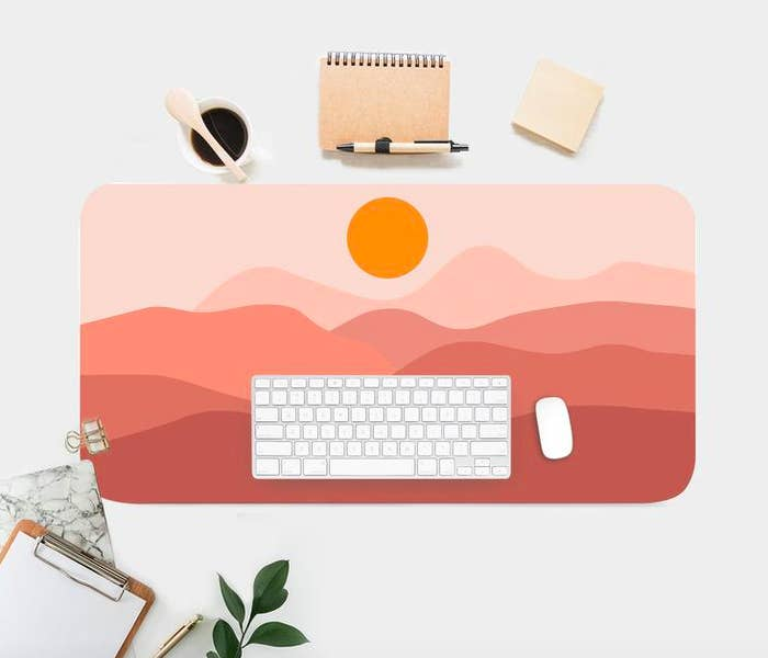 A flatlay of a large desk mat printed with a graphic sunset