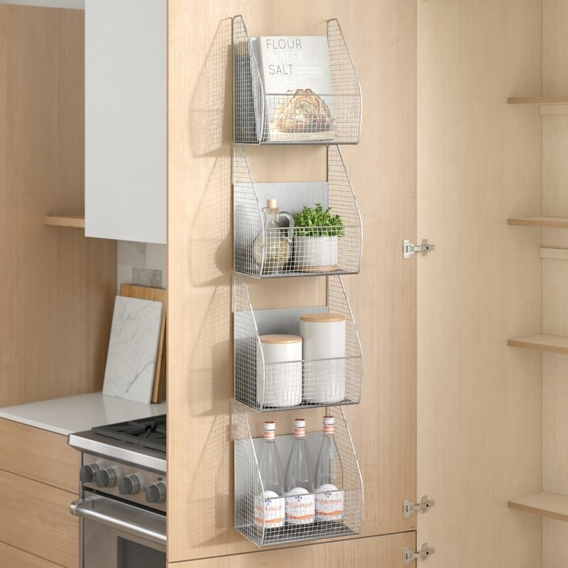 A shelving unit made of four metal baskets mounted on a cabinet door holding water bottles, jars, cookbooks, and a plant.