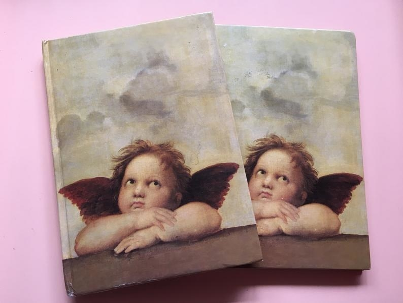 """Two notebooks featuring one of the two cherubs of featured in Raphael's Sistine """"Madonna"""""""