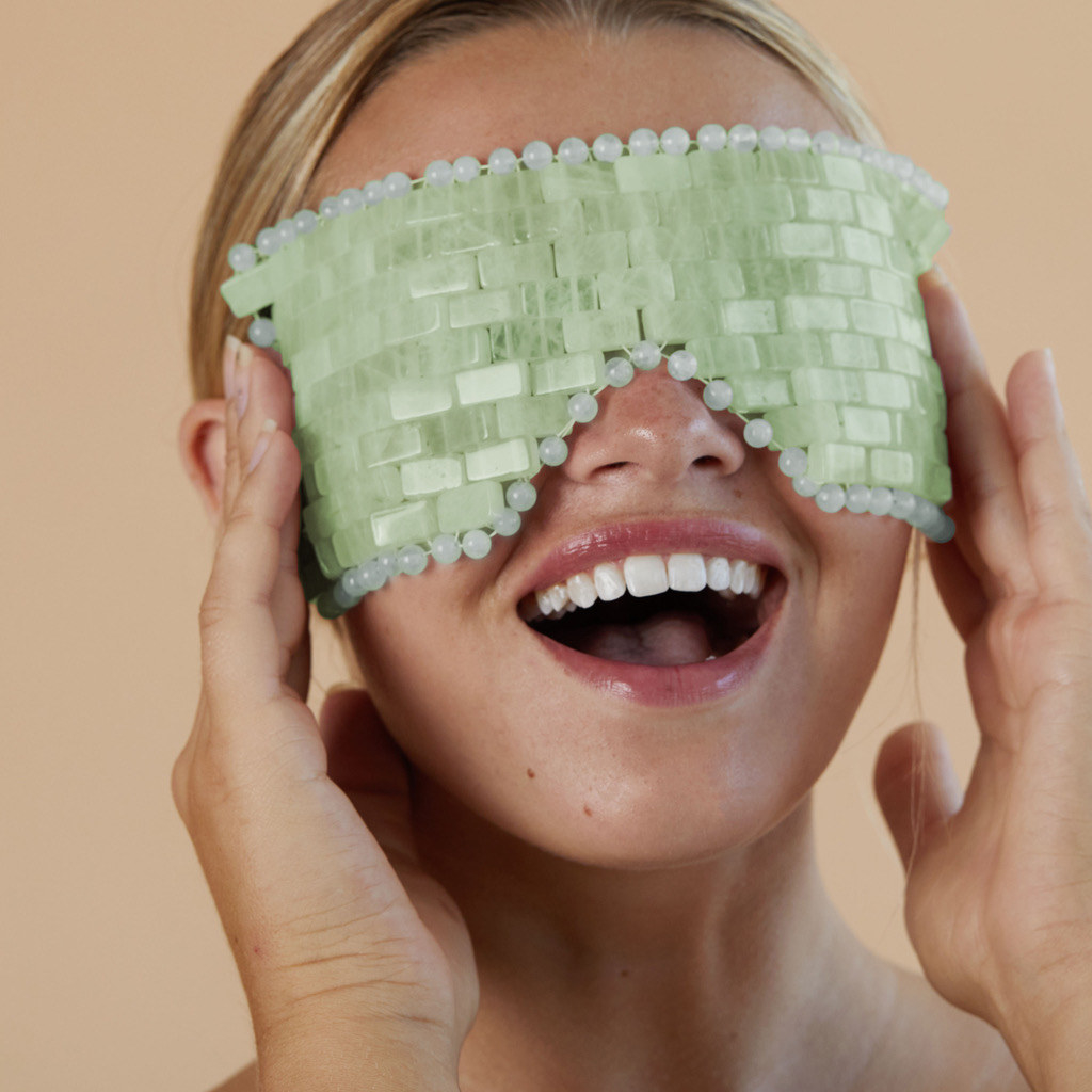 A smiling person places the jade eye mask over their face