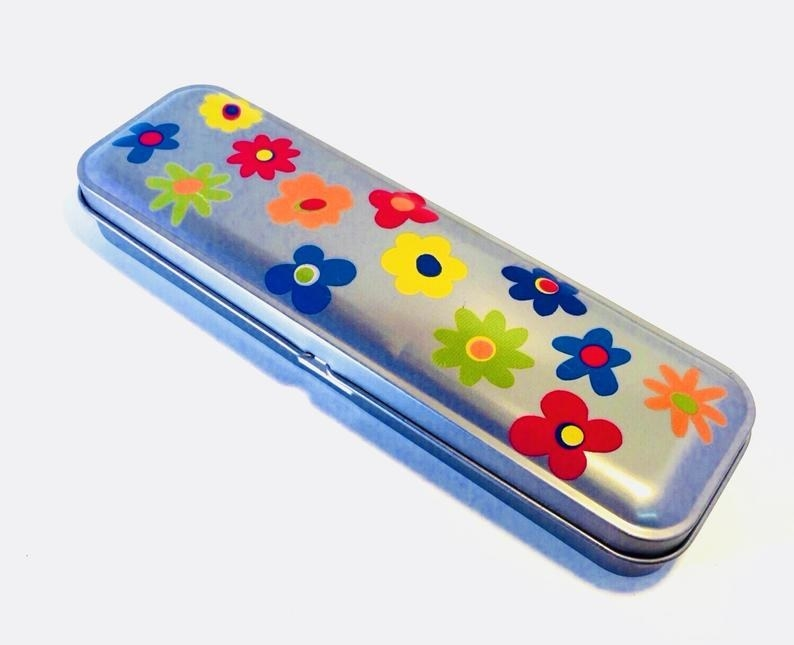 A tin pencil case with early '70s style flowers on it