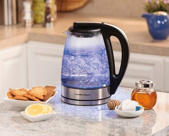 electric tea kettle on kitchen counter with biscuits honey and lemon