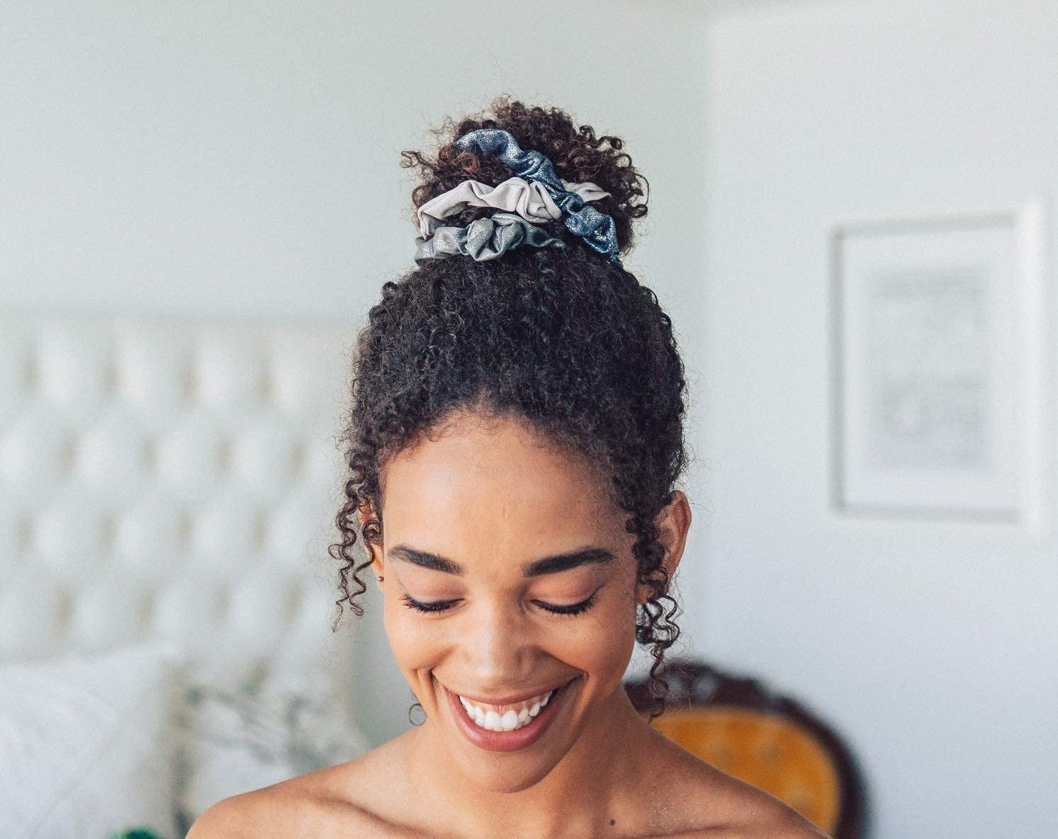 A smiling person wears the scrunchies in a high bun