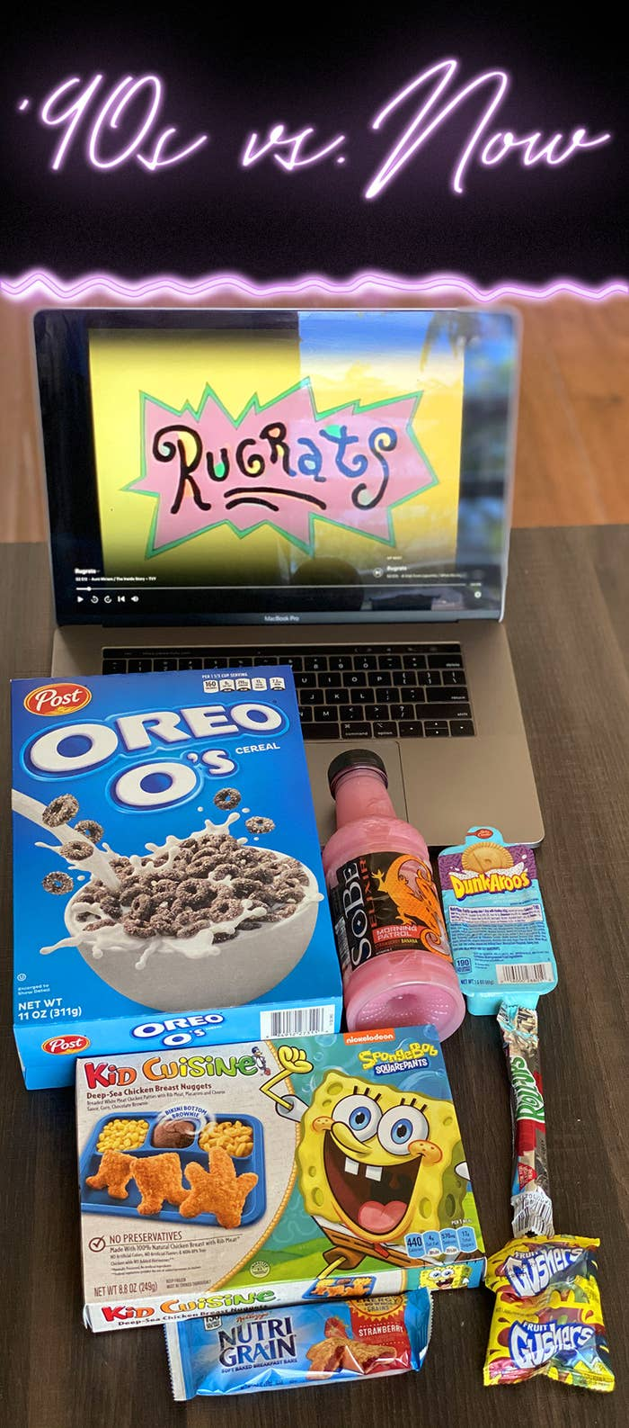 A laptop displaying Rugrats, a box of Oreo O's cereal, a bottle of Strawberry banana SoBe, DunkAroos cookies, a Kid Cuisine frozen meal, a Fruit Roll-Up, a Nutri-Grain bar, and Fruit Gushers