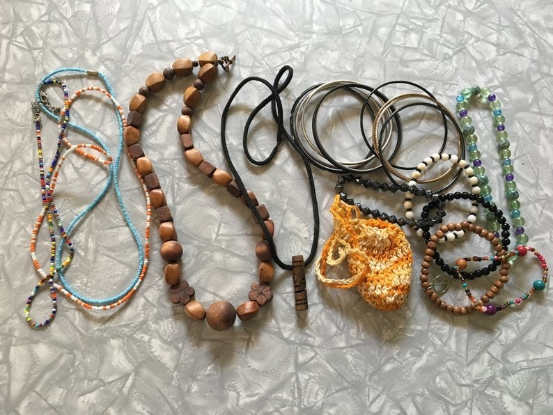 A bunch of different style of necklaces, beads, wood, next to beaded bracelets and silver bracelets