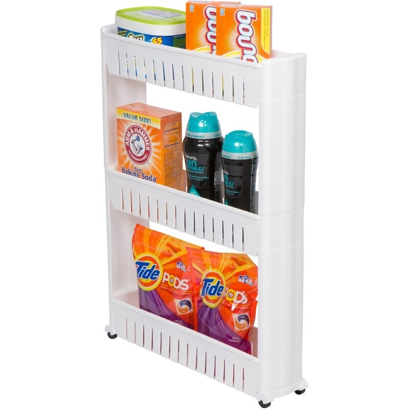 A white, plastic cart on caster wheels with three shelves holding laundry supplies