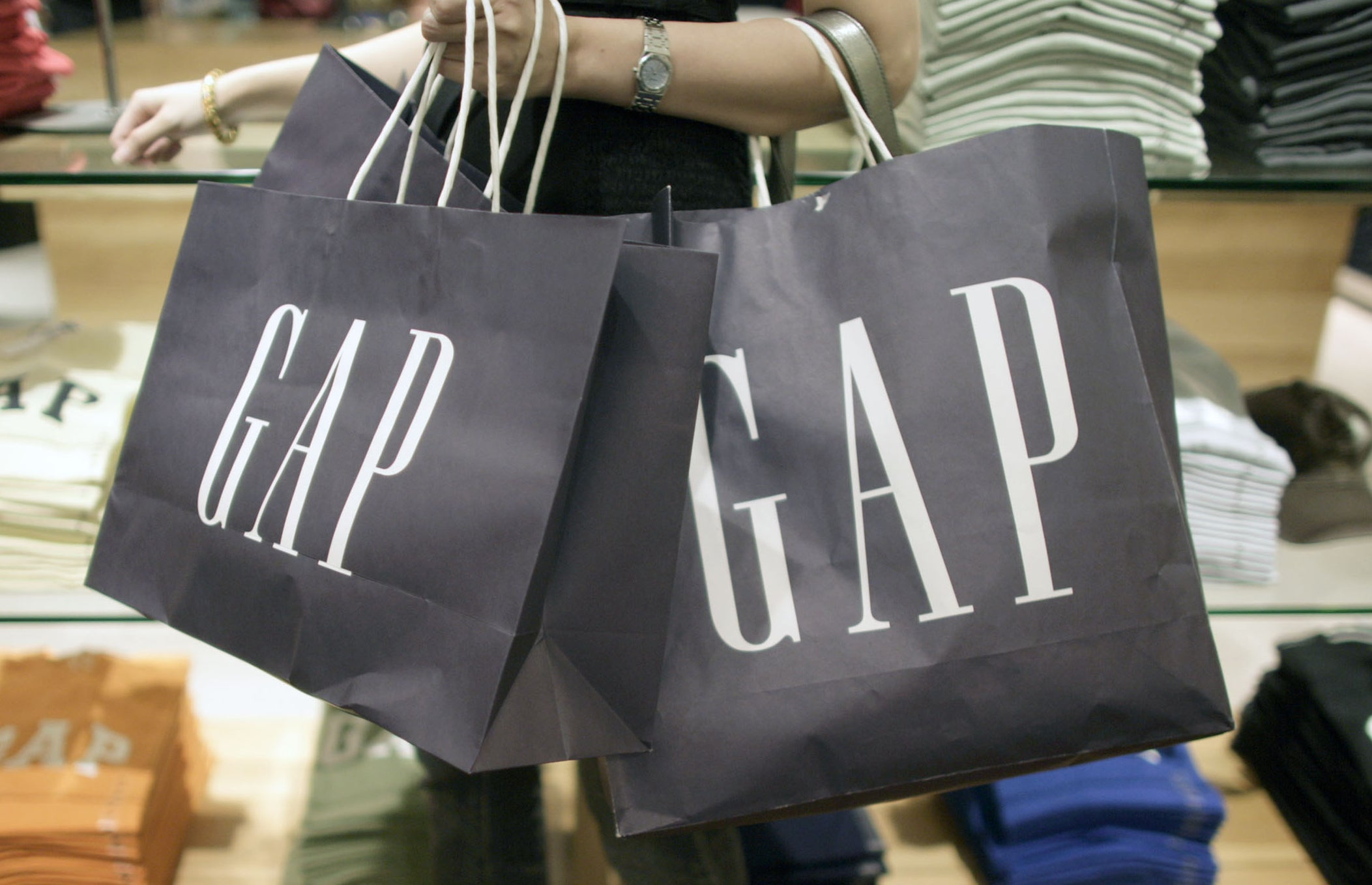 A arm holding three navy blue GAP paper bags