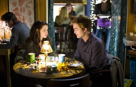 Still from Twilight: Bella and Edward sitting together at a table in a restuarant