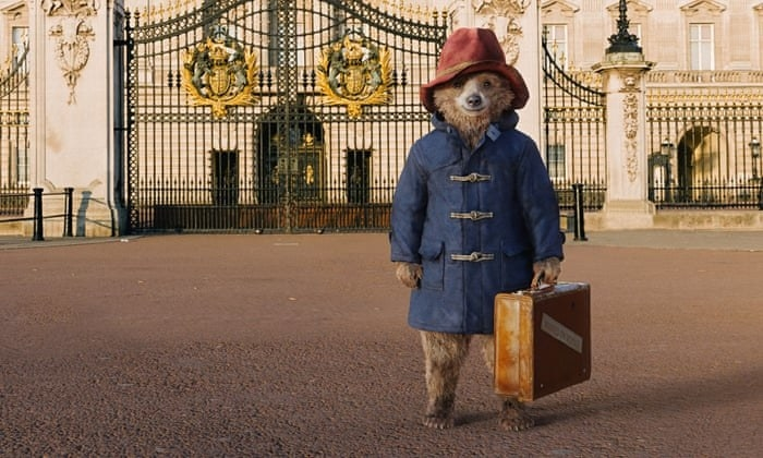Paddington wearing a blue coat and red hat, standing in front of Buckingham Palace in London. He is holding a briefcase