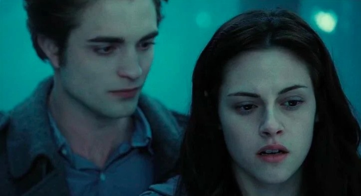 Still from Twilight: Edward standing behind Bella, who is looking concerned