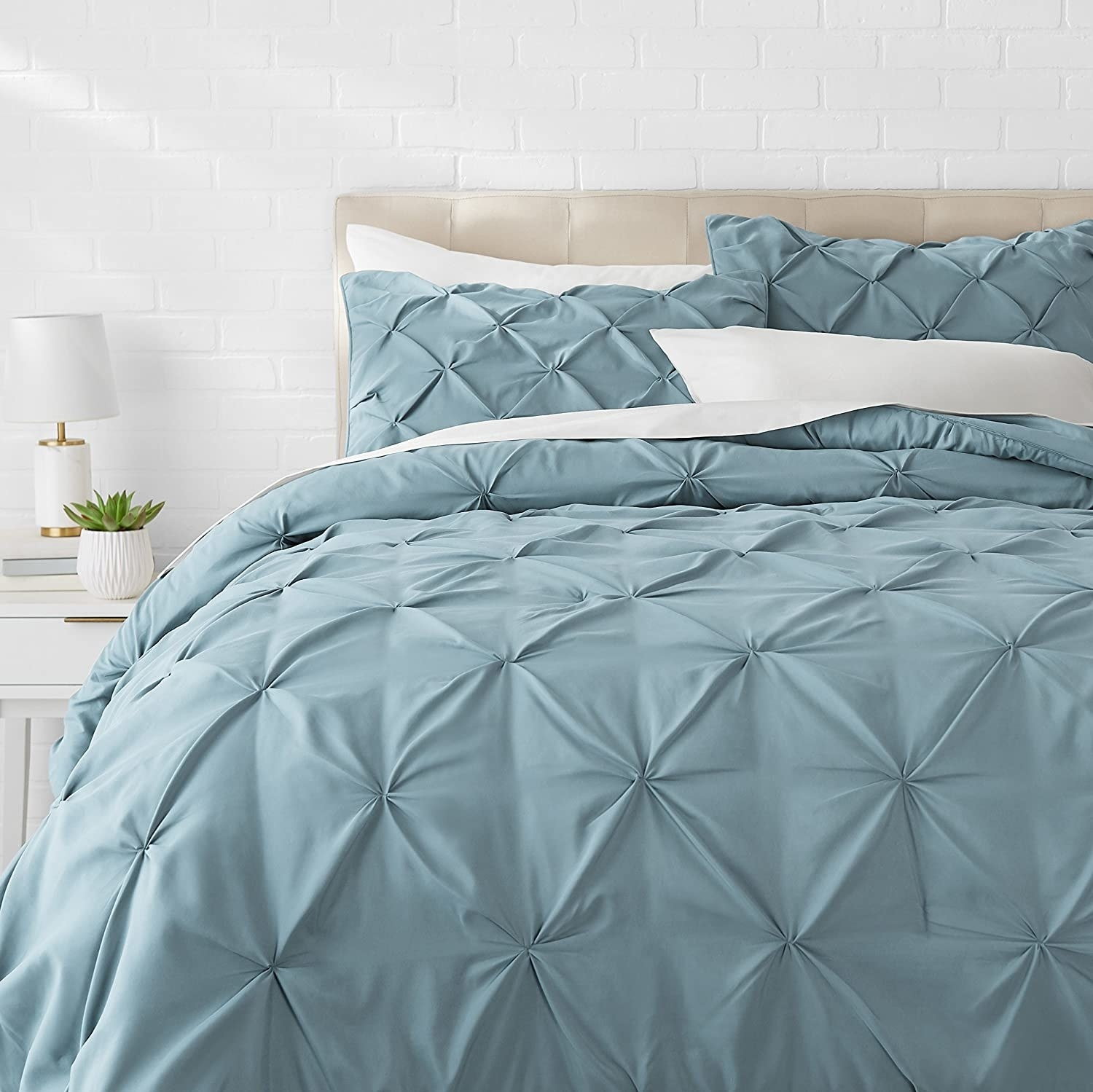The pinch pleat comforter and shams on a bed in front of a white brick wall