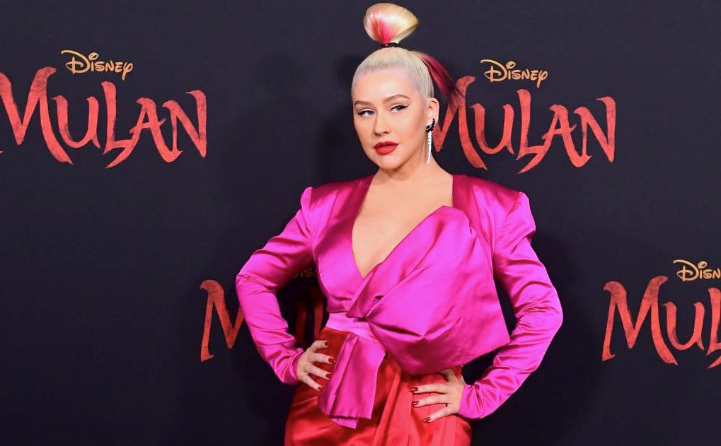 Christina Aguilera poses on the Red Carpet for the Mulan premiere in the bright pink dress and up do