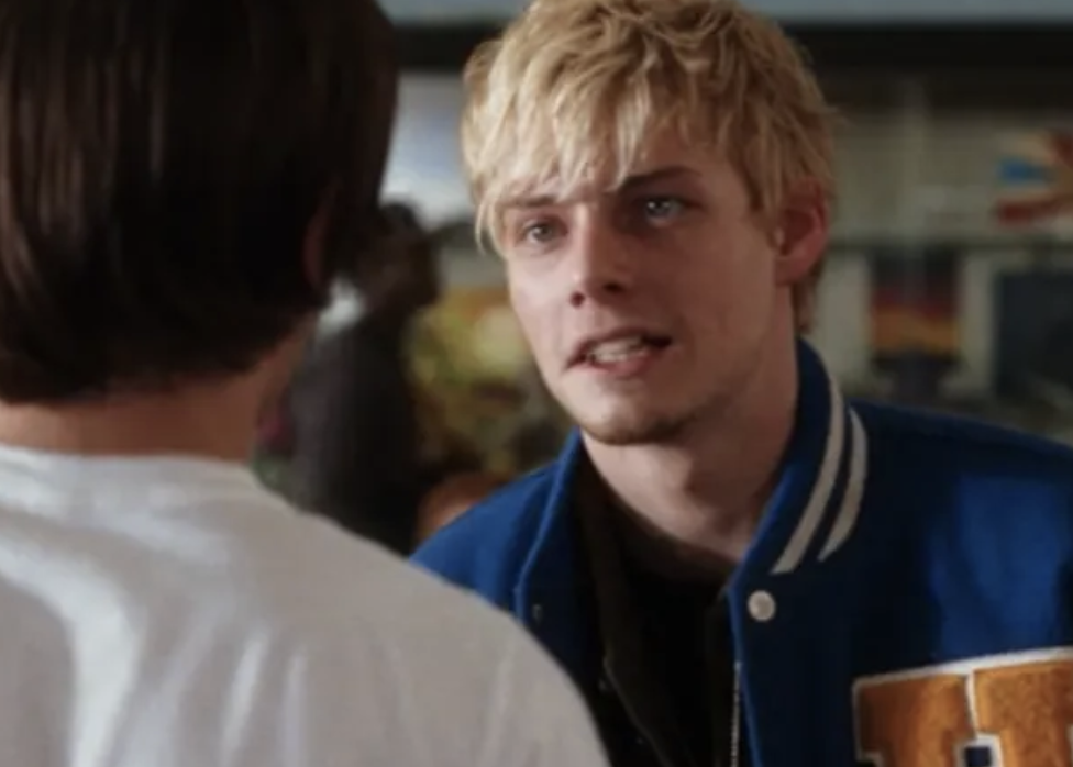 Stan wearing an athletic jacket, staring at Mike in the cafeteria, intimidating him