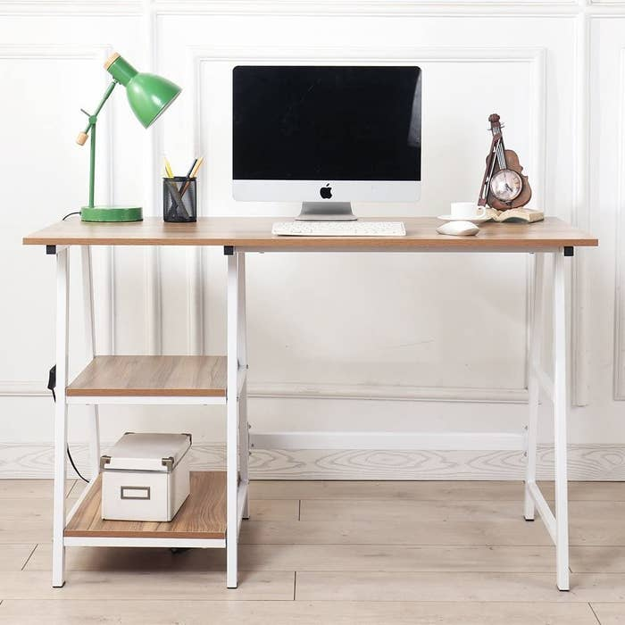 A small wooden desk with a laptop and lamp on the top There are two built-in shelves underneath with a small box on one