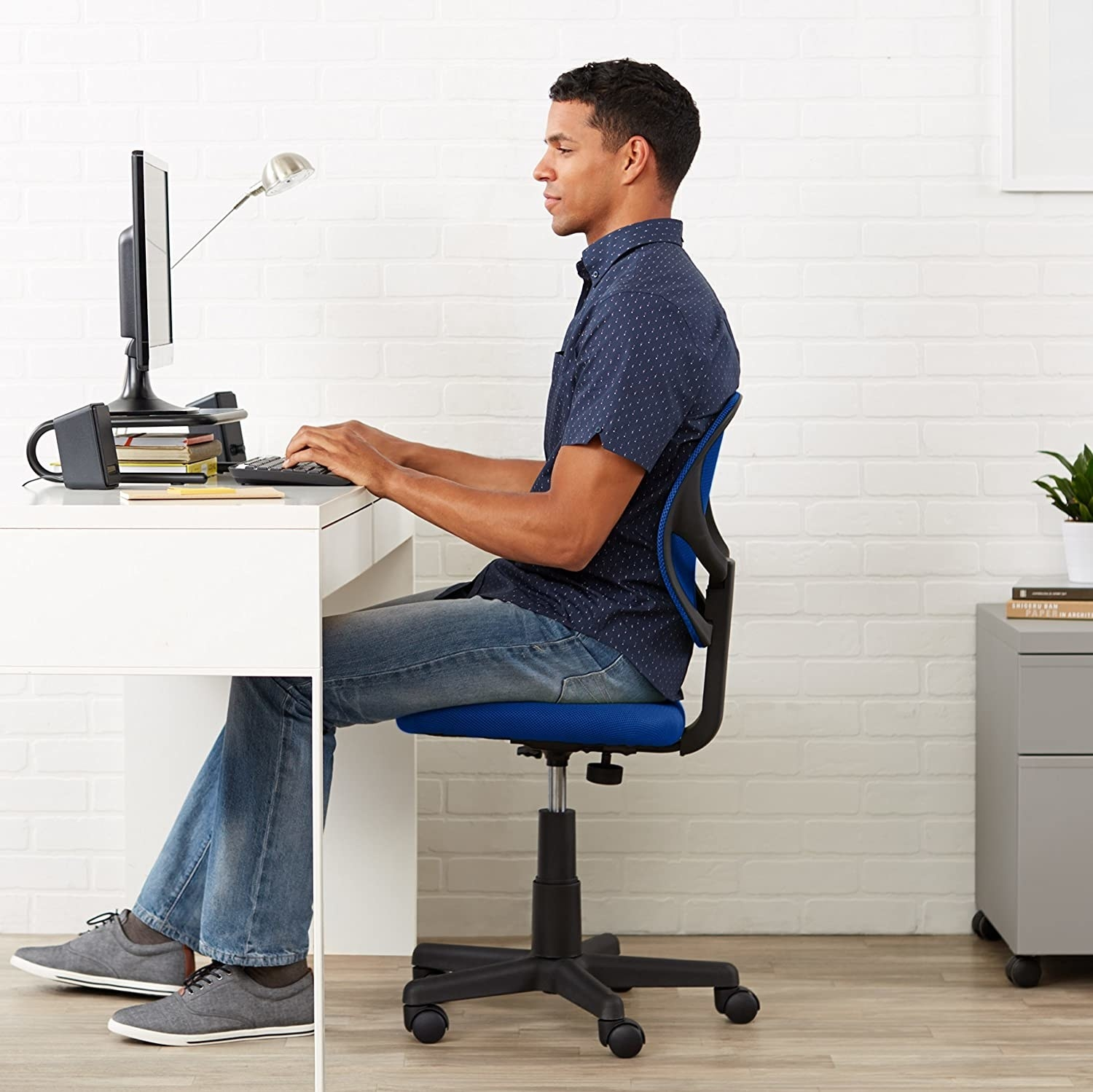 A person sitting at their desk on a chair with wheels