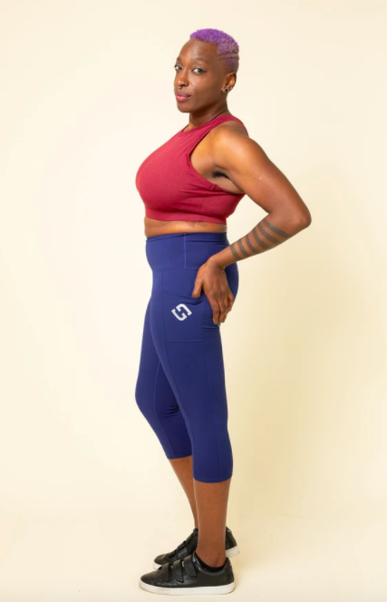 Model wears dark blue capris with a red crop top and black sneakers