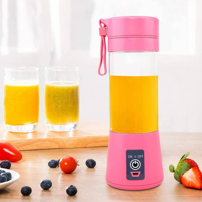 The blender filed with an orange smoothie next to various berries and two glasses filled with smoothies