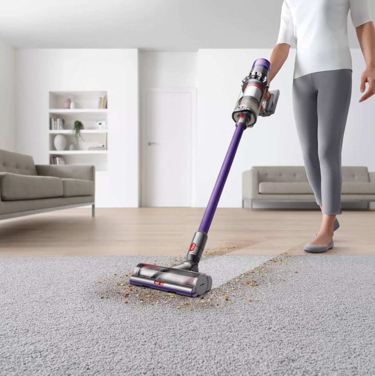 Dyson being used to vacuum up a mess on a carpet