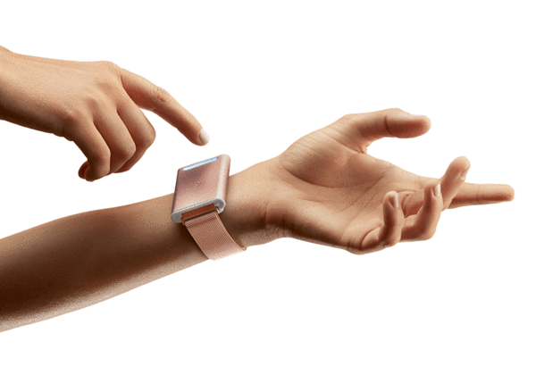 The Embr Wave on a model's wrist in pink with the other hand touching the square head