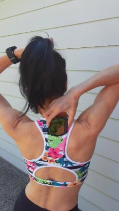 Reviewer slides smartphone into back pocket of floral racerback sports bra
