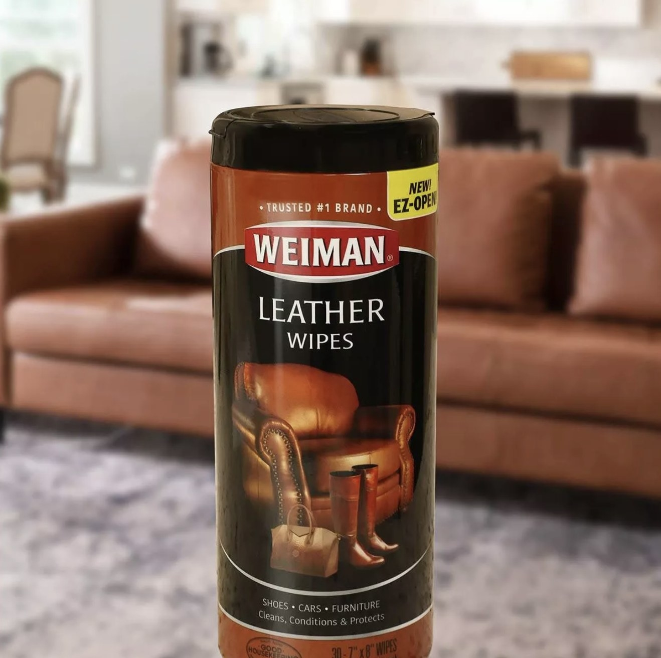 """Black container that says """"Weiman Leather Wipes"""" next to a brown couch"""