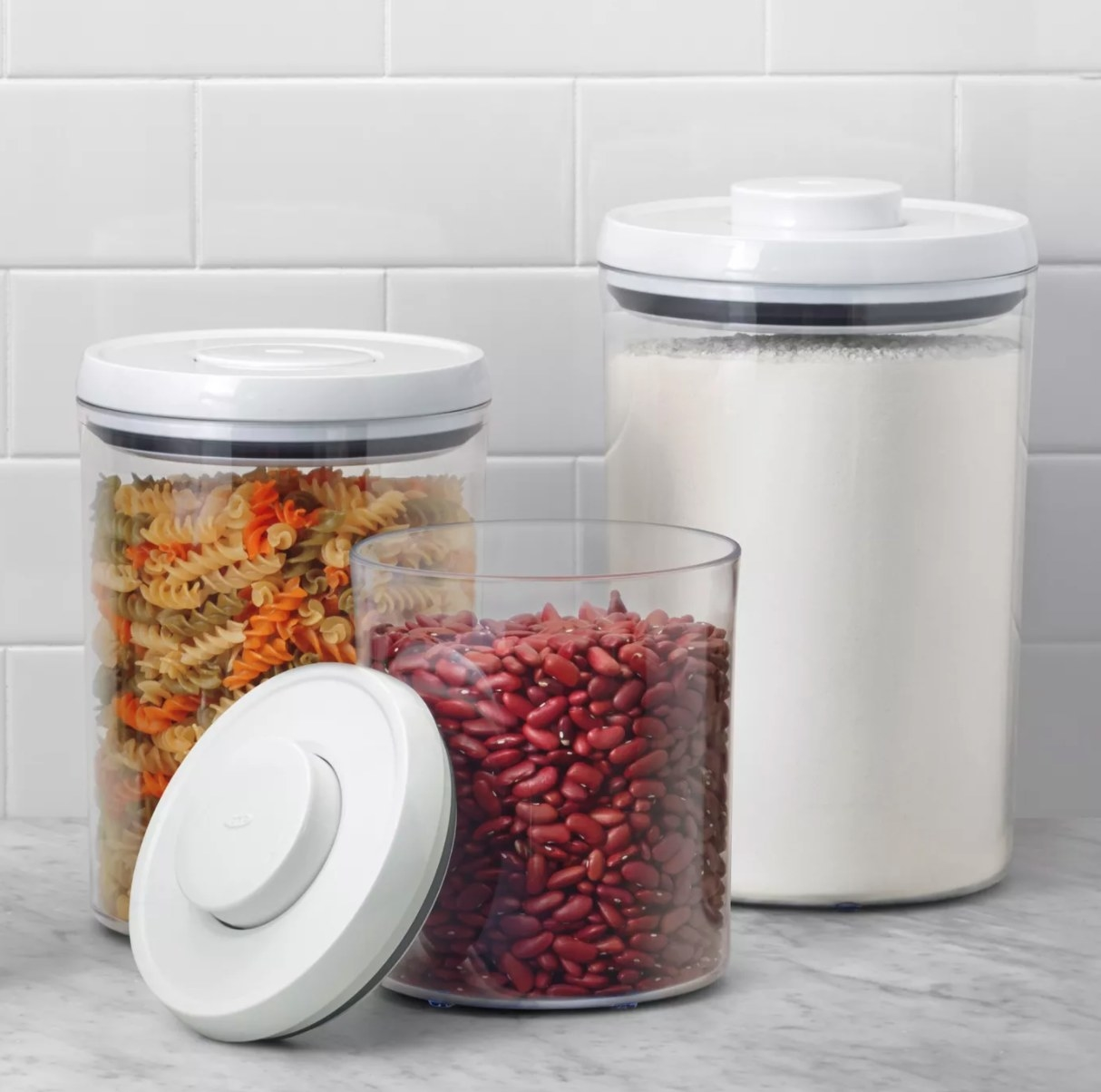 The set of three canisters with noodles, flour, and beans in them
