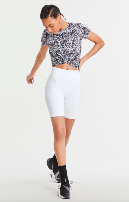 Model wears black-and-white print knot-front tee with white bike shorts