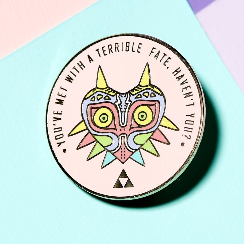 "the pink circular pin with the words ""you've met with a terrible fate haven't you?"" around the top rim above a pastel-colored version of the character"