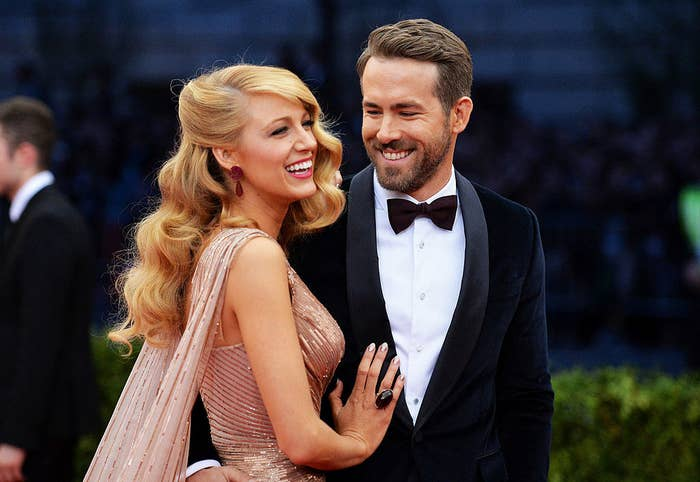 Blake Lively and Ryan Reynolds smiling on a red carpet