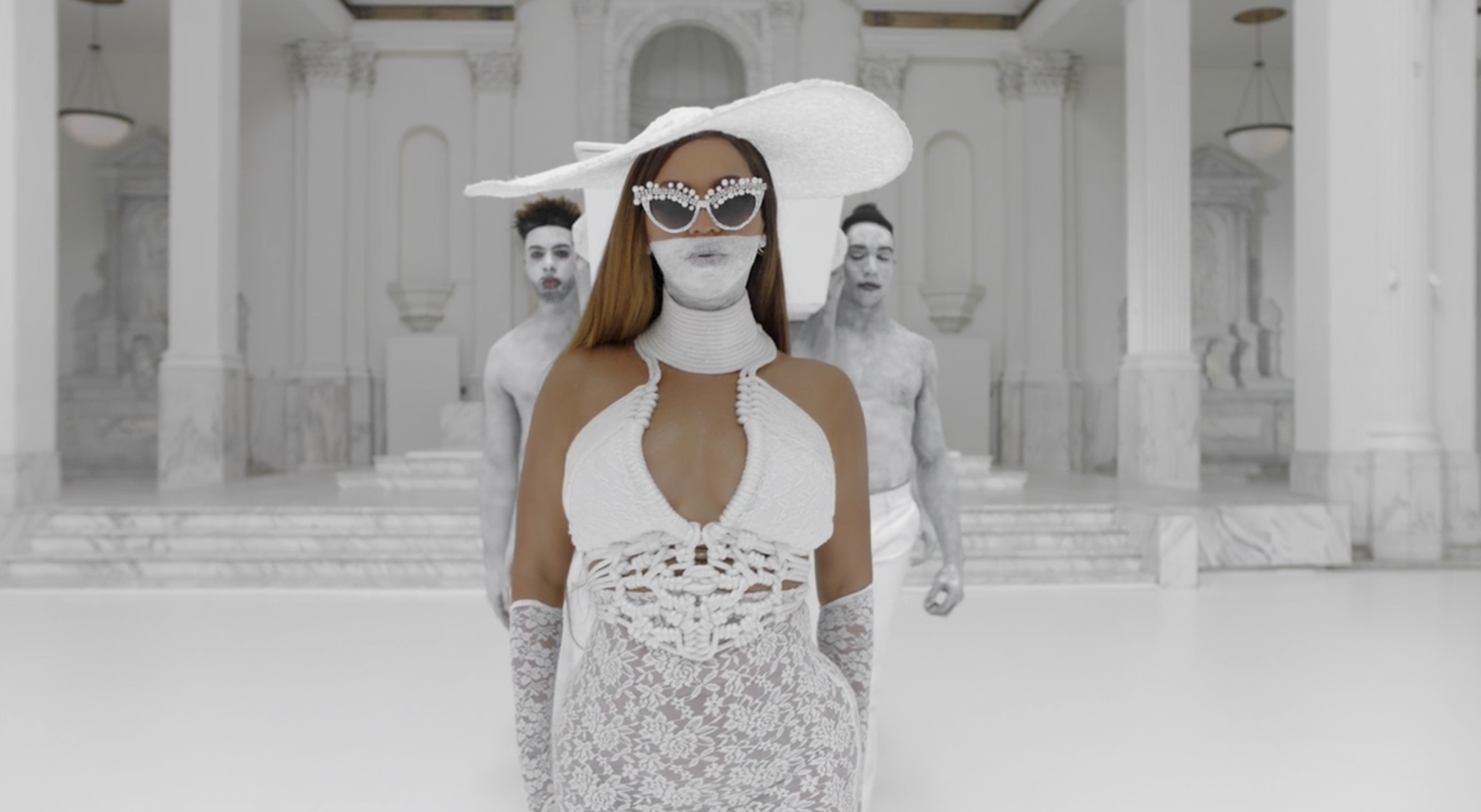 Beyoncé with a white dress made of rope at the top and lace at the bottom