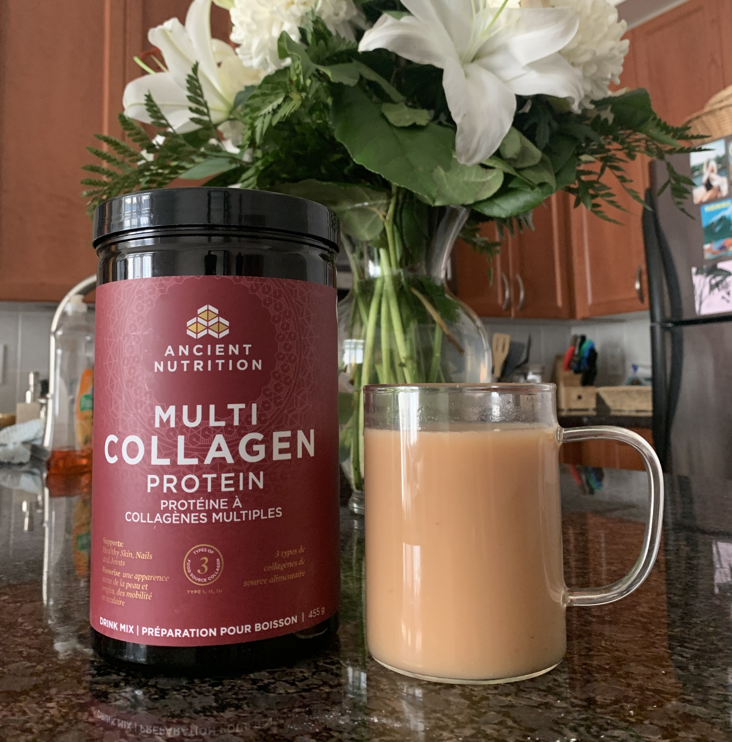 A container of Multi Collagen Protein drink mix next to a mug of the product mixed with water
