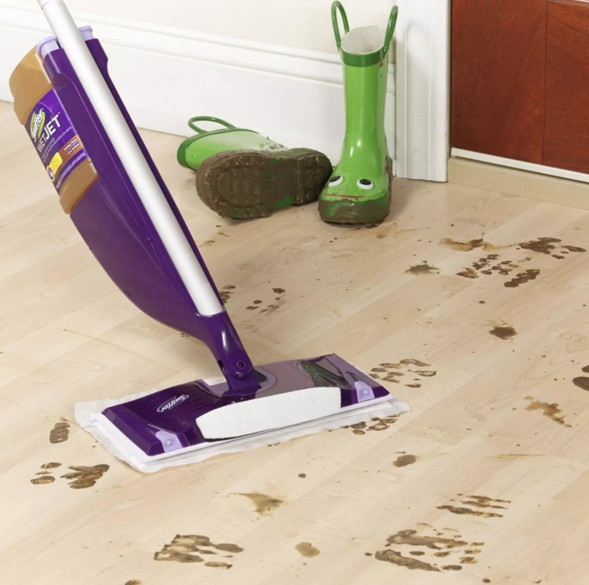 The swiffer being used to clean muddy footprints