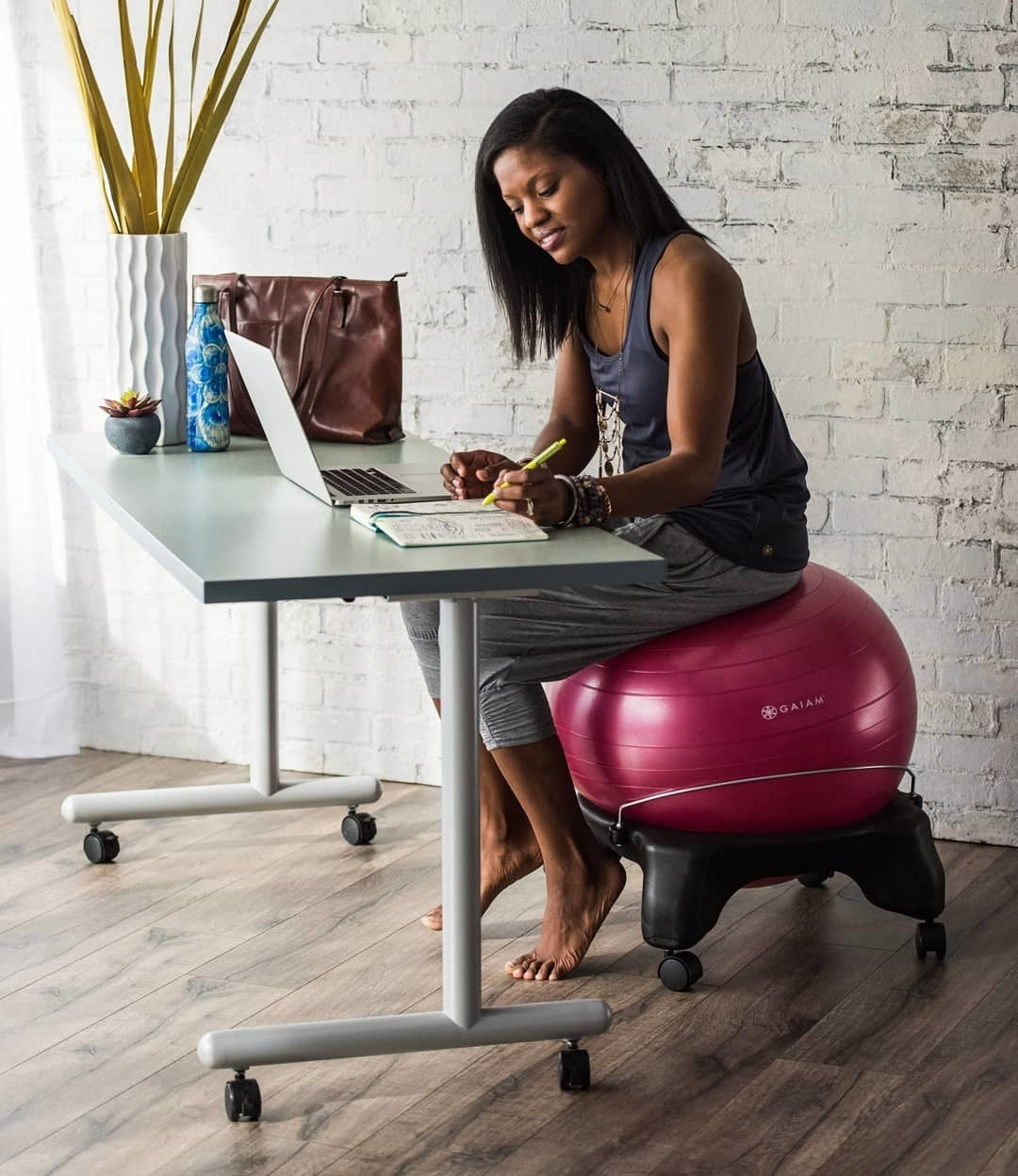 A person working a desk and sitting on a yoga ball. The ball is nestled in a short frame that has wheels on the bottom