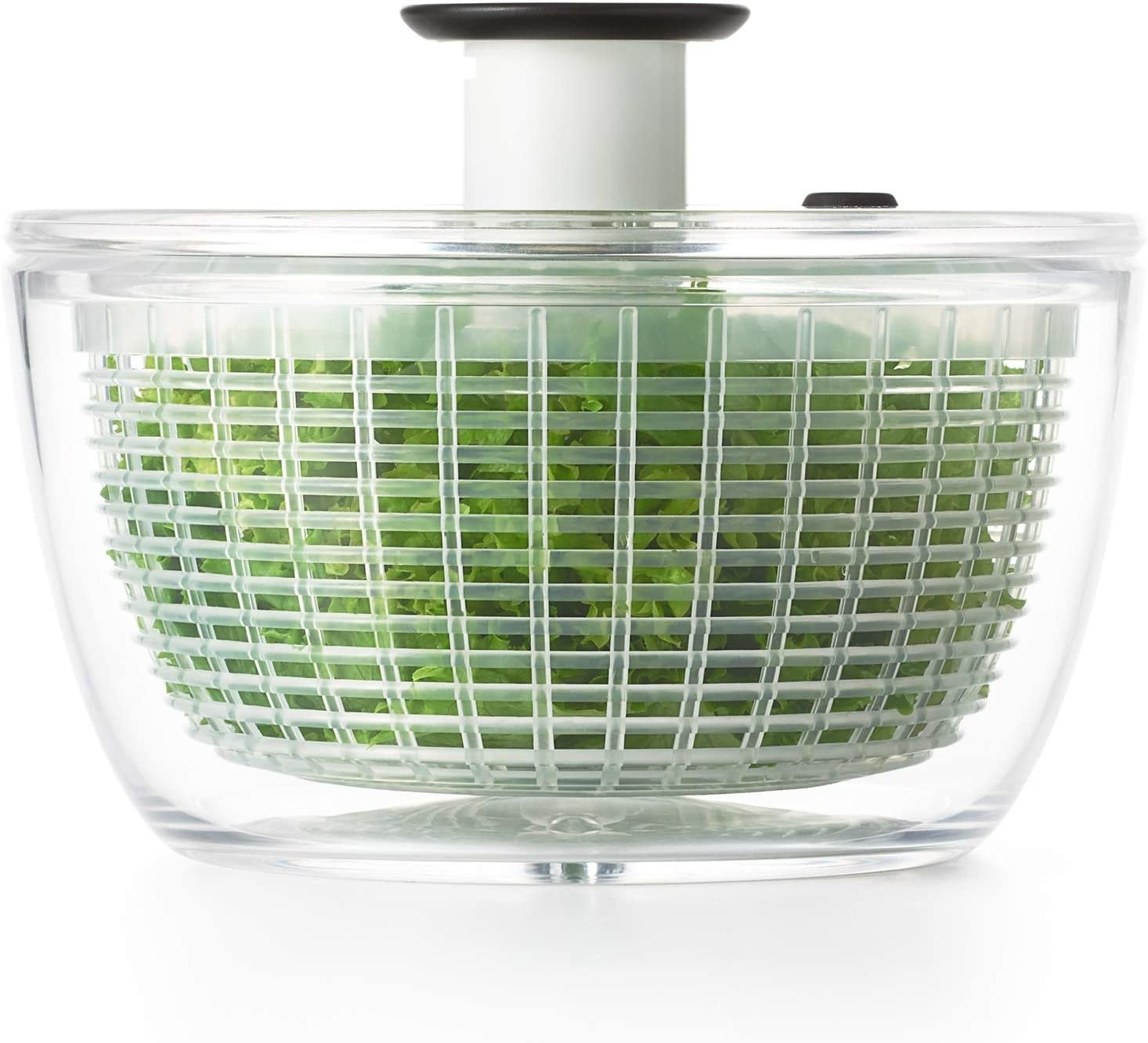 A salad spinner with lettuce inside of it.