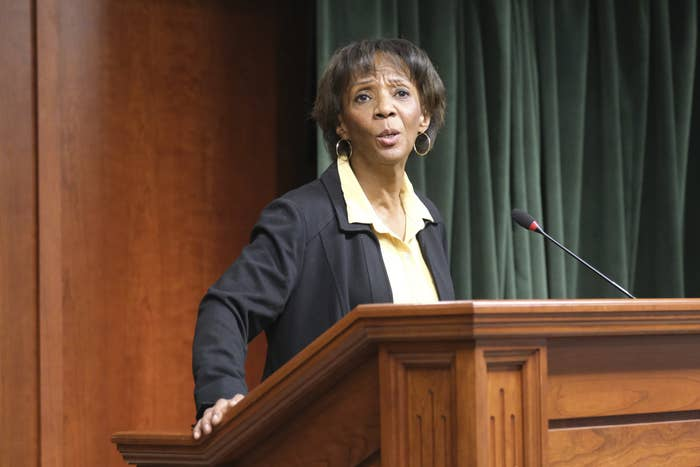 Jackie Lacey speaks at a wooden podium into a microphone.