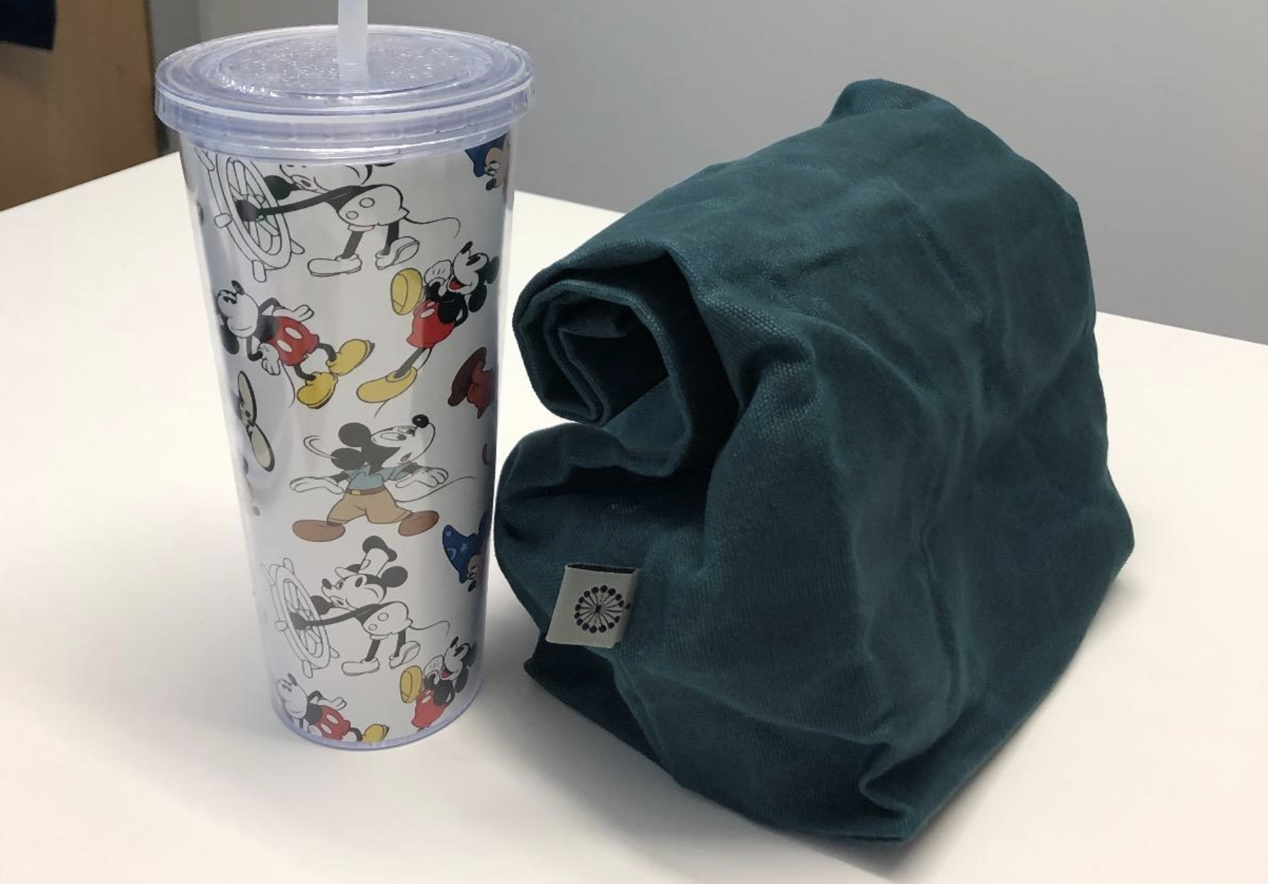 A dark green canvas bag shaped like a paper lunch box rolled up