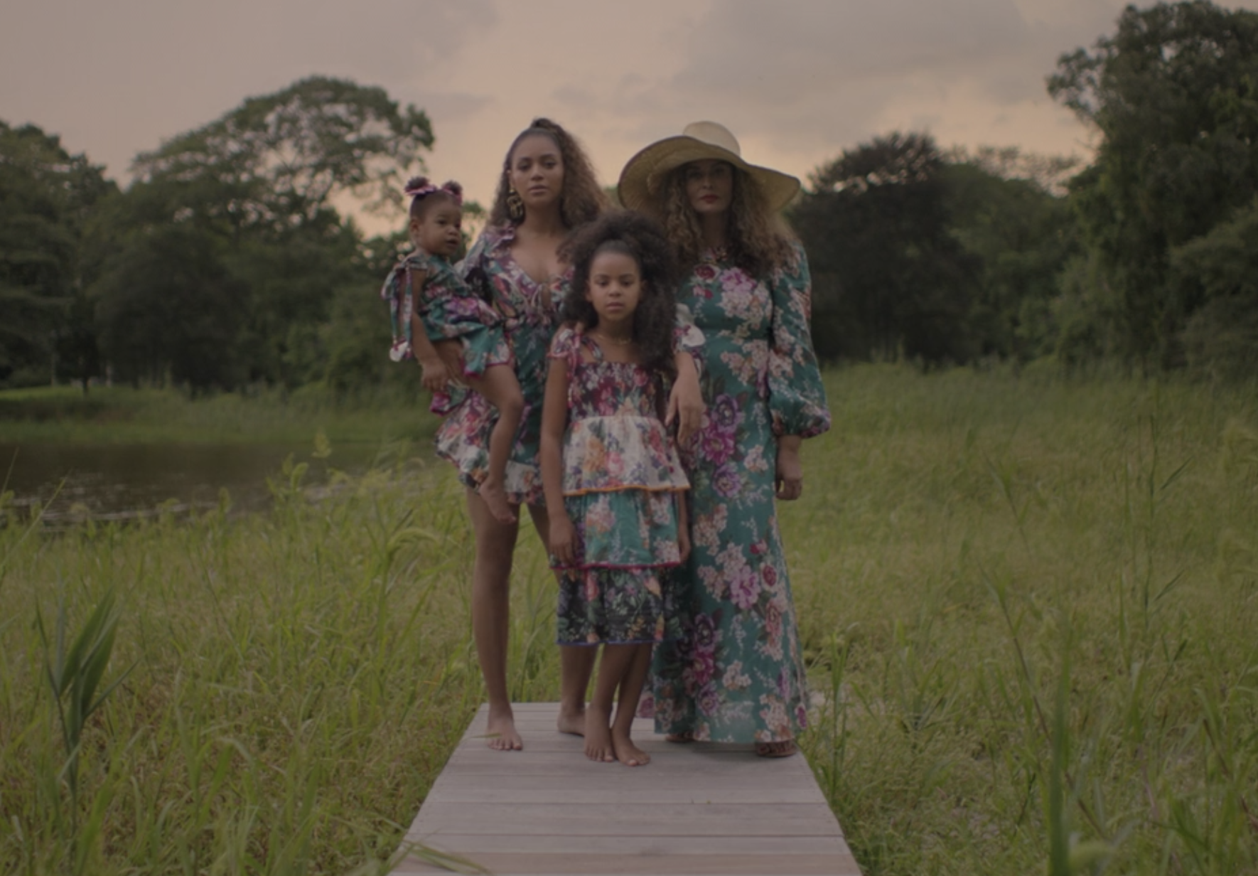 Tina Knowles, Beyoncé, Blue Ivy, and Rumi standing together in matching floral outfits