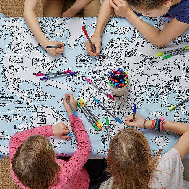 Four kids sit around the World Map Coloring Tablecloth, coloring in with markers