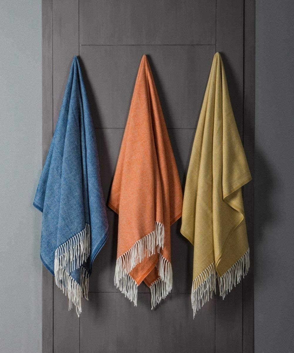 A blue, orange, and yellow blanket with white fringe on the ends handing from a door