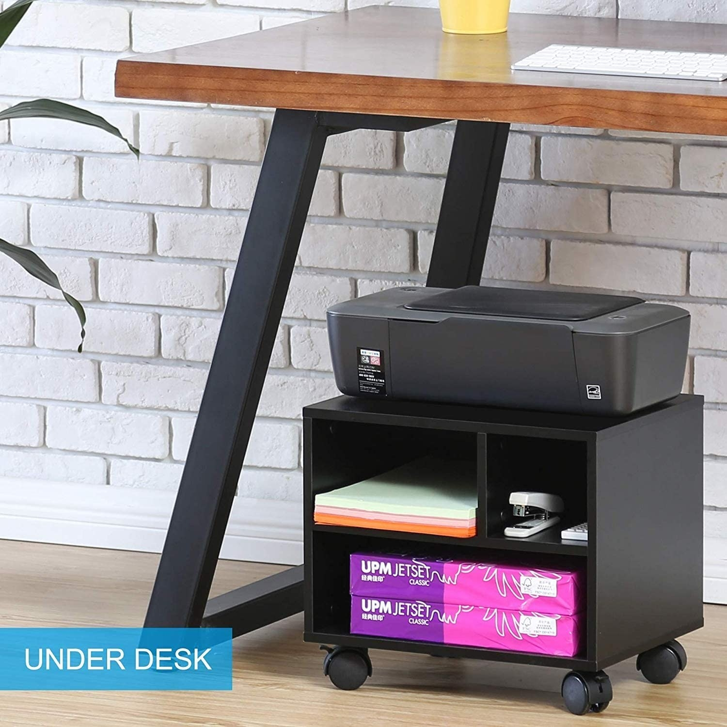 A printer sitting on a small wooden shelf on wheels The shelf has three sections filled with office supplies like paper and a stapler