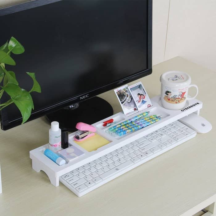 A long rectangular stand placed over a keyboard on a desk. The stand has a coffee mug, pens, pictures, a stapler, and lip balm organized neatly on top