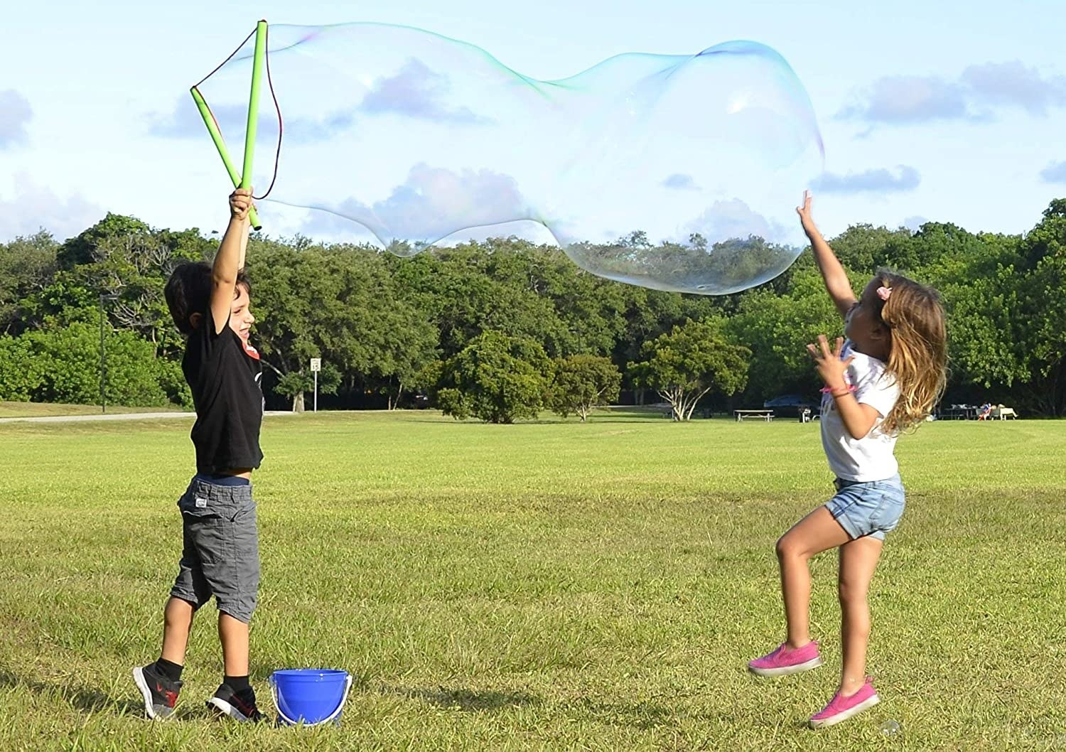 two kids playing with the bubble maker with a giant bubble coming out of their net