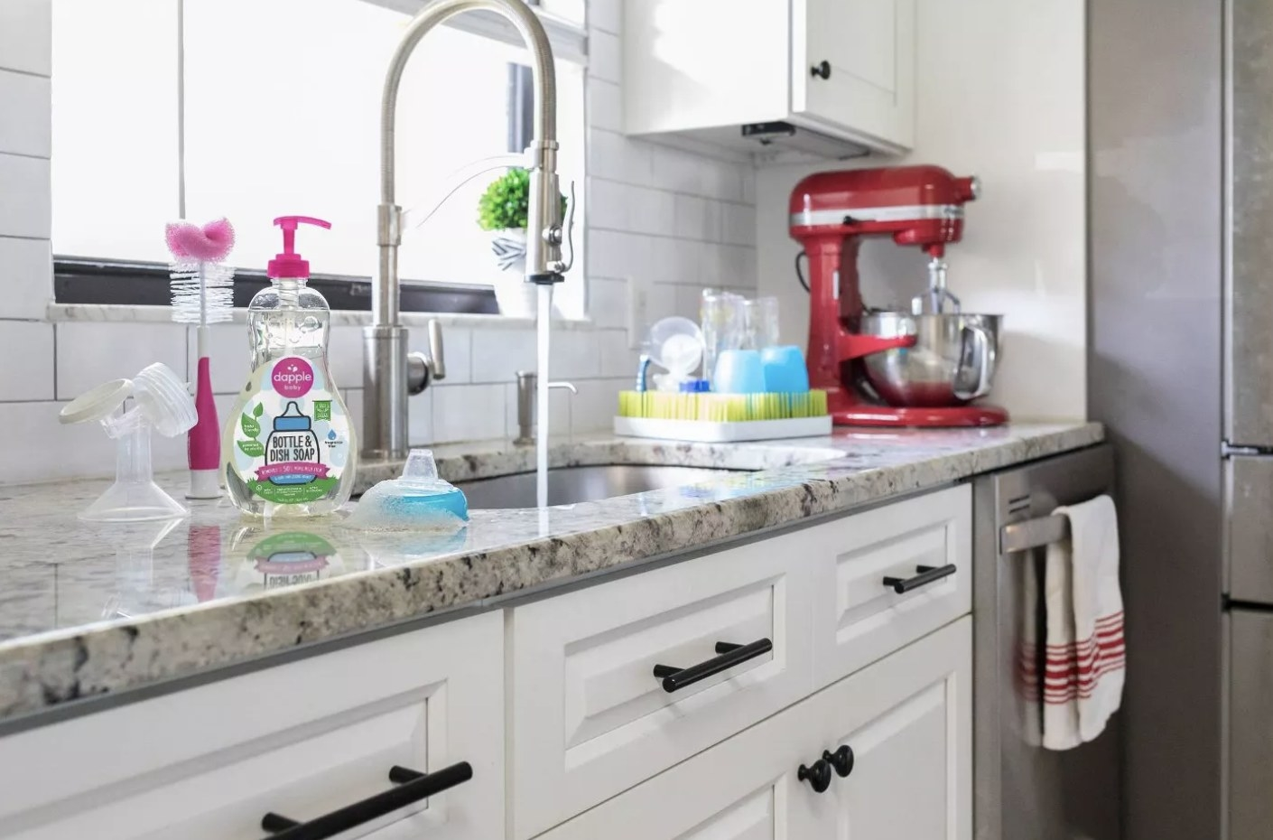 Pink and clear bottle of Dapple Bottle and Dish Soap next to a silver sink