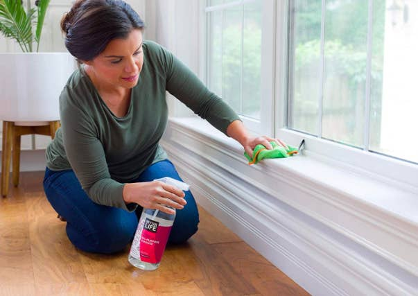 Model uses clear and pink bottle of Better Life Pomegranate All-Purpose Cleaner to clean windowsill